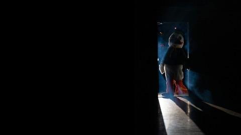 A dark room with the Oregon Duck entering through the door.